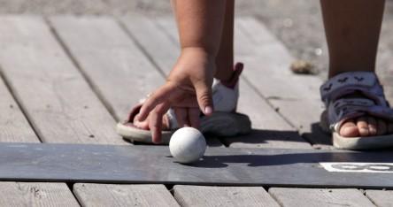 Närbild på barns hand som precis lagt golfbollen på plats för spel.