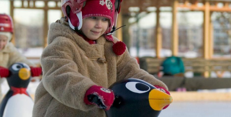 Barn med hjälm och vinterjacka åker skridskor tillsammans med Pingu.