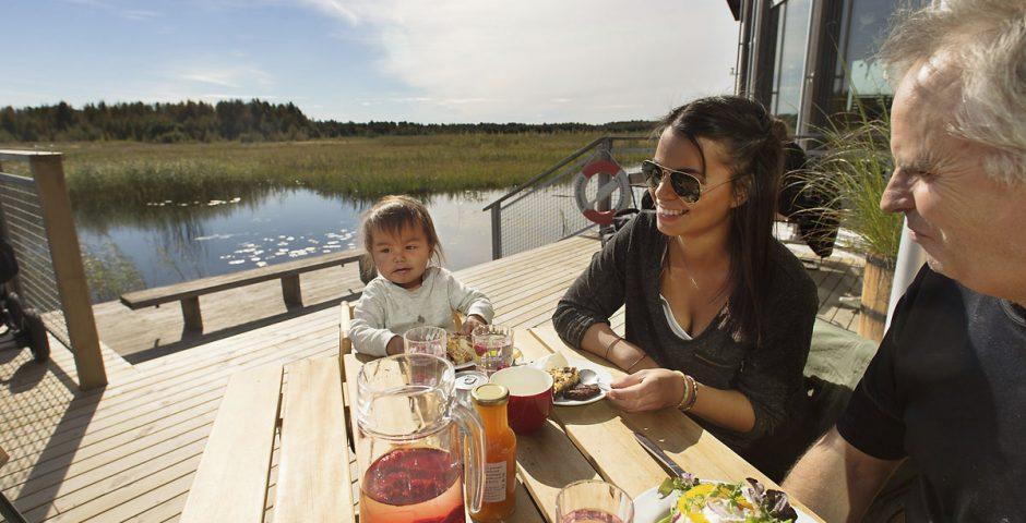 Morfar, dotter och litet barnbarn fikar tillsammans på bryggan till Naturum Värmland. I bakgrunden syns vattnet glittra, näckrosor och vassen på strandängarna.