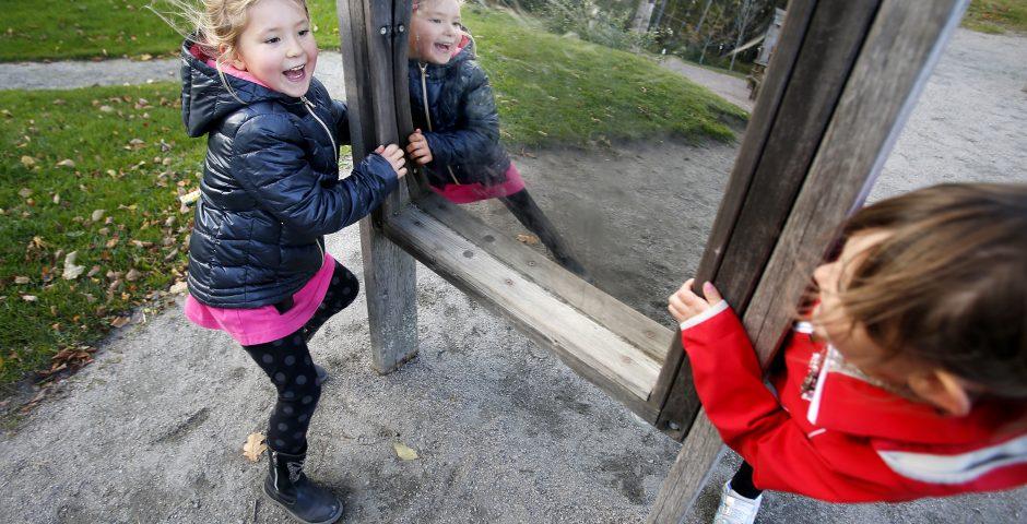 Två flickor leker skrattande vid en illusionsspegel. De har höstjackor på sig.