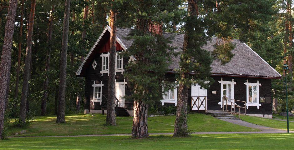 Acksjöns kapell, en stugliknande träbyggnad, syns mellan tallarna.