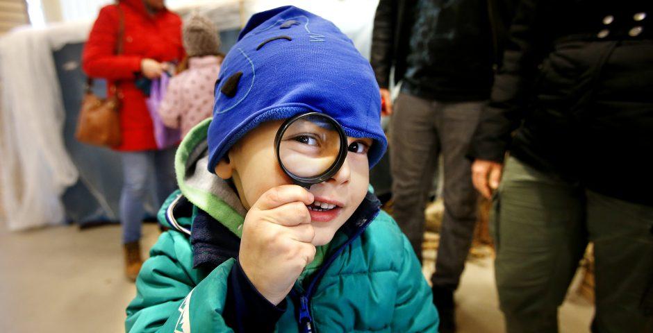 Pojke tittar in i kameran genom ett förstoringsglas.