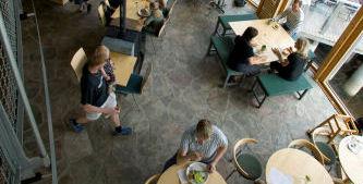 Miljöbild tagen uppifrån på kaféet i Naturum Värmland. Folk fikar vid flera runda bord, nära panoramafönstren ut mot Mariebergsviken.