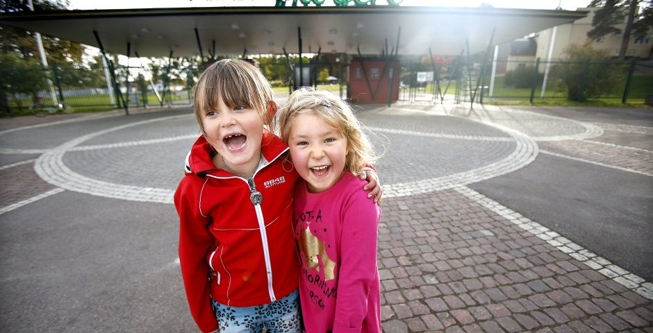 Två glada flickor framför huvudentrén till Mariebergsskogen.