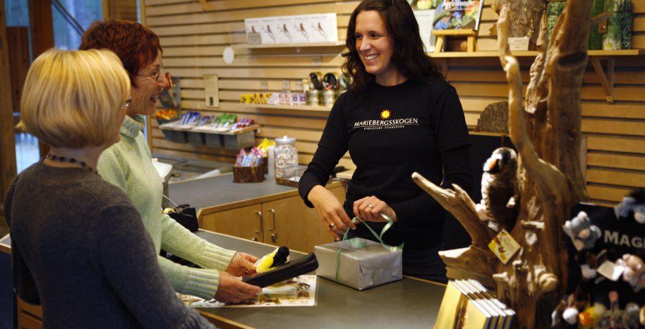 Personal i naturums butik slår in paket åt två kvinnor.