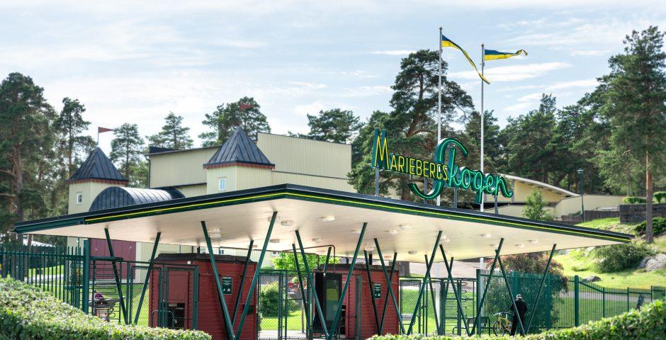 Huvudentrén till Mariebergsskogen. I förgrunden formklippt häck, vimplarna vajar i vinden och i bakgrunden syns Friluftsteatern.
