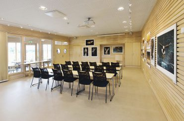 Inifrån lokalen Skogsstjärnan, med stolar och bord möblerat i skolsittning.