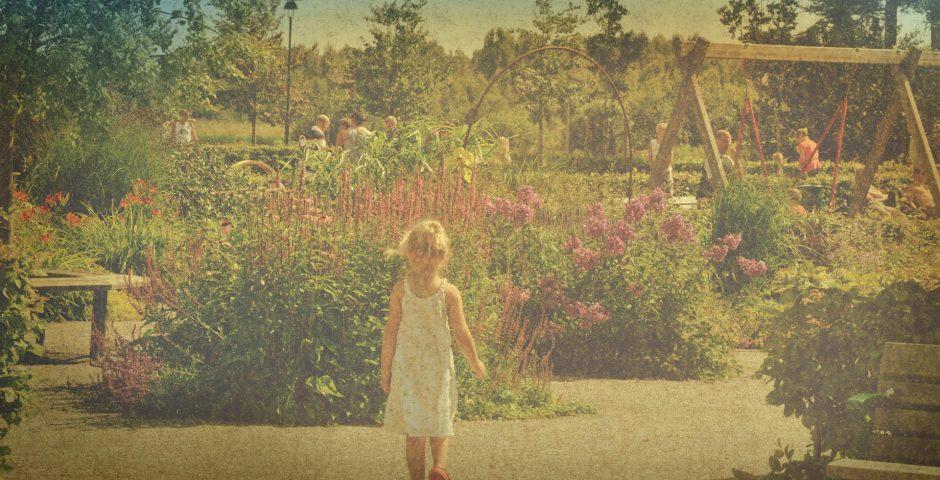 Flicka på väg mot blommorna i konstträdgården, Lekträdgården en varm sommardag.