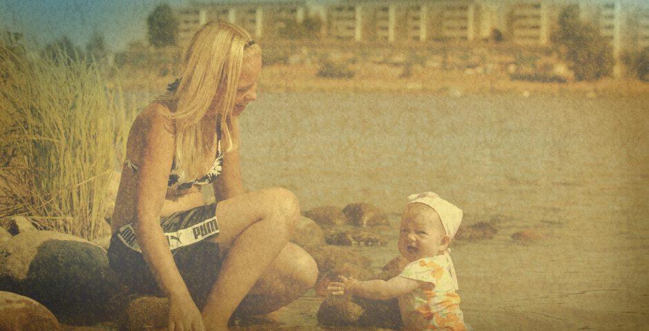 Mamma och bebis badar i vattenbrynet.