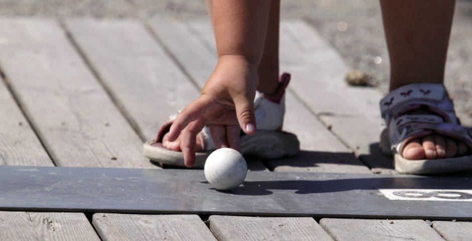 Närbild på en barnhand som sträcker sig efter en bangolfboll.