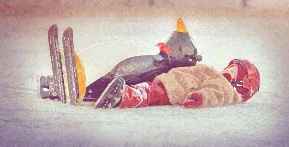 Flicka med hjälm, skridskor och vinterjacka ligger på rygg på isen bredvid Pingu.