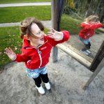 Flicka leker framför illusionsspegel i Lekträdgården.