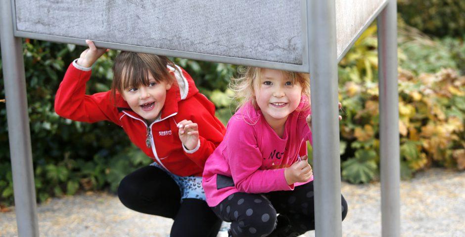 Två flickor leker glatt i Lekträdgården.