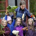 Trädgårdsmästare tillsammans med fyra flickor som stolt har skördat grönsaker i Barnens köksträdgård.