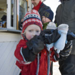 Flicka håller upp ett par skridskor, som hon precis har hyrt i kiosken.