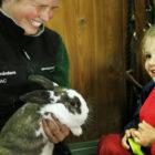 Djurvårdare visar upp en kanin för ett barn.