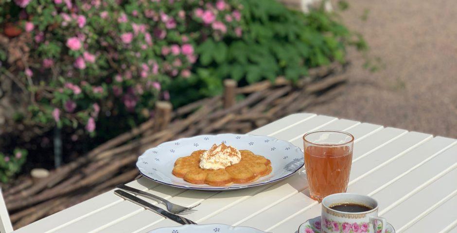 Nygräddade våfflor med sylt och grädde, uppdukat utomhus. Kaffet serveras i gammaldags rosenkoppar.
